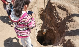 Zahara Taleb watches an unexploded bomb being removed from her father's farmland.