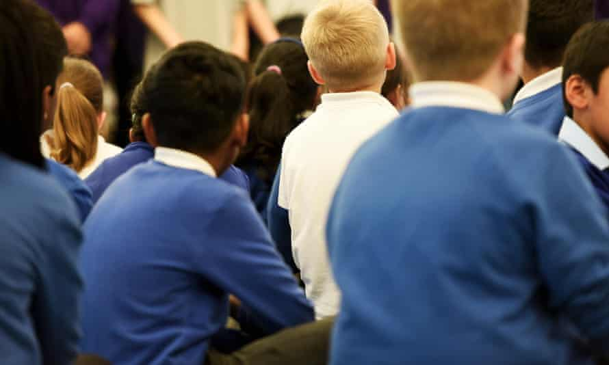 Young primary school aged children sit in a school assembly
