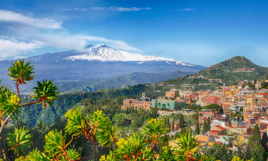 A panoramic view of Taormina with Mount Etna behind it