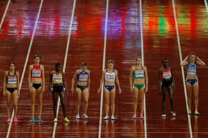 Runners wait in the rain for the start of a heat of the women's 3,000m steeplechase.