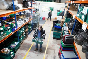 The centre's warehouse manager, Dave Woodward, moves a crate of tins.