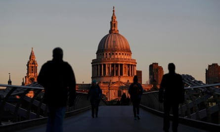 People walk towards St Paul's Cathedral during sunrise in central London