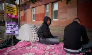 Afghan refugees Rahman Sahah (left) , 32 and Mirwais Ahmadzai, 27, sit outside the Home Office in Glasgow, Scotland, last month