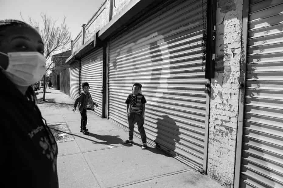 Kimberly White Smalls and her grandsons Kelsey E. Smalls Jr, 8, left, and Donovan E. Smalls, 9, right, stand outside a closed store that has still not been able to reopen after Hurricane Sandy on the corner of Beach Channel Drive and Beach 43rd Street in the Edgemere neighborhood of Far Rockaway, Queens on April 6, 2021. Smalls grew up in the neighborhood and had to flee her family home when Hurricane Sandy hit.
