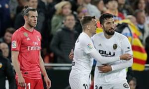Valencia's Ezequiel Garay celebrates with Denis Cheryshev as Gareth Bale looks on.