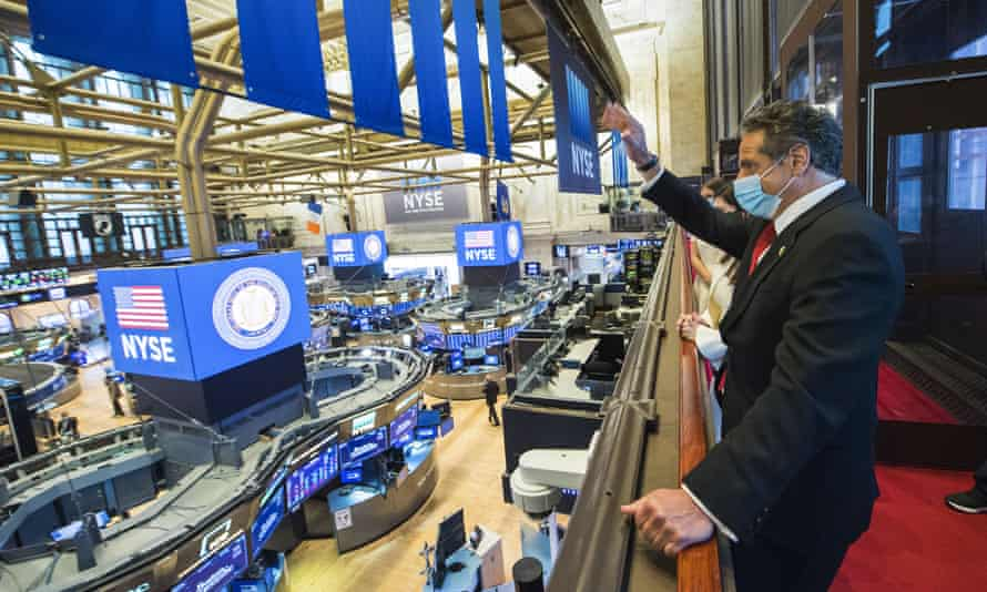 The New York governor, Andrew Cuomo, waves to the trading floor at the New York stock exchange on Tuesday