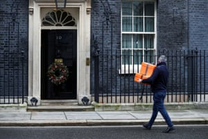 A person carries presents into No 10 Downing Street in London, UK
