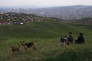 Mongolian people resting with their dogs on a hill with houses situated on the slope in the background in Ulan Bator.