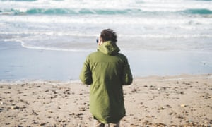 Rear view of man looking out to sea from windy beach