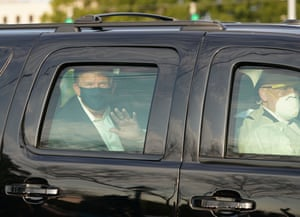 Donald Trump waves from the back of a car outside Walter Reed medical center in Bethesda, Maryland.