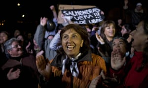 "People shout slogans as they listen to a speech during a protest on Chiloe Island, Chile. The sign in the background reads in Spanish: ""Salmon farms out! Free Chiloe."" Local residents blame large-scale salmon farms for the algae bloom."
