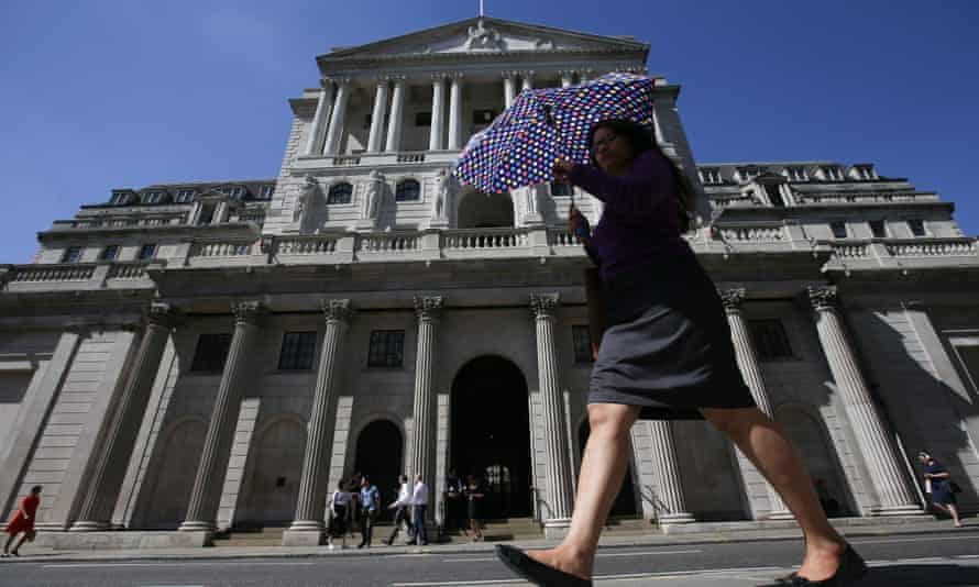 Pedestrians walk past the Bank of England
