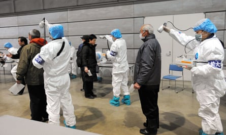 Japanese medical personnel check people for radiation exposure