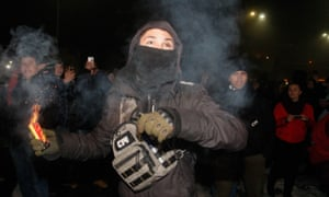 A protester with a smoke grenade at the Russian embassy in Kiev on Sunday.