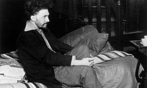 American poet and critic Ezra Pound sitting on his bed in his Paris studio in 1923.