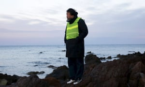 Ai Weiwei stands at a beach where refugees and migrants arrive daily on the Greek island of Lesbos,