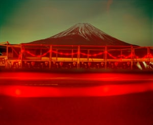"""Roadworks and Mount Fuji, Near Kawaguchiko, Japan, 1999""""Ask just about anyone what comes to mind when they think of Japan and they will reply — Fuji. The night I made this image, I stopped at some road works and Fuji-san was visible. I made a 4-minute exposure and the flashing red lights combined with the green fluorescent light of Fujinomiya city reflecting from the clouds was almost hallucinogenic"""" -Chris Steele-Perkins"""