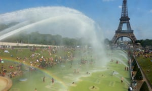 People cool off in and around a large water pool at Trocadero, across the Seine from the Eiffel Tower.