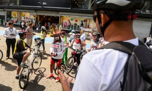 A volunteer for World Car Free Day gives opening remarks to cycles for a city bike tour.