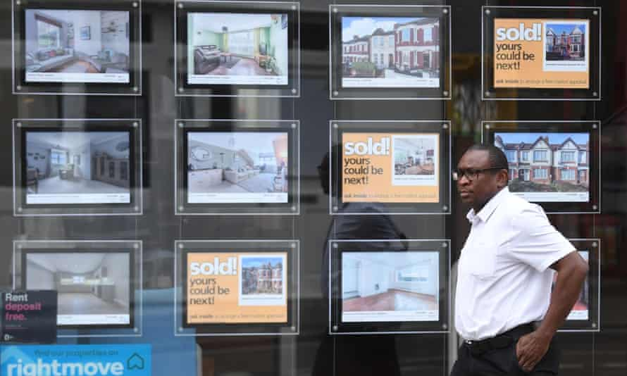 A person passes properties advertised at an estate agent in London, Britain.