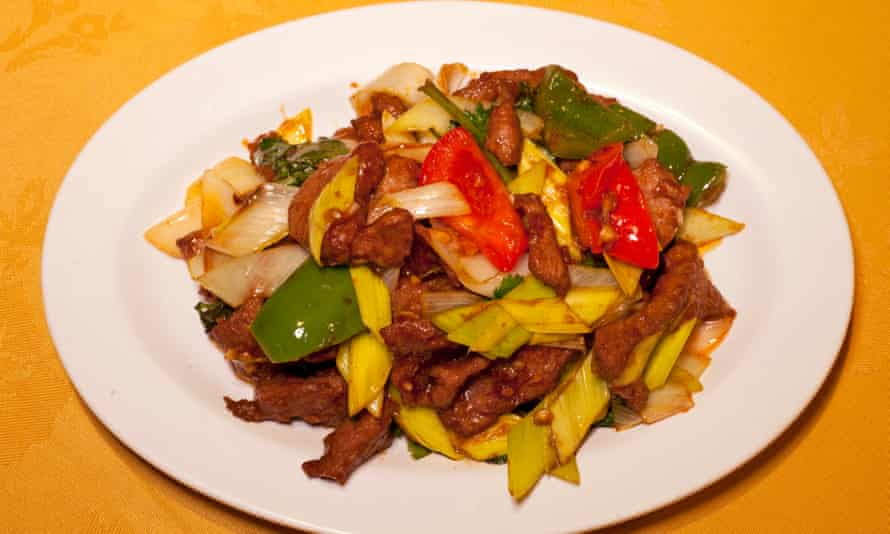 Ginger lamb with chunks of red and green pepper on a round white plate