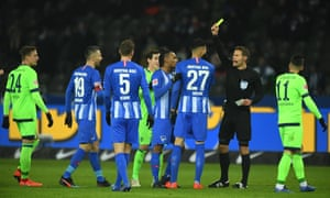 Referee Felix Brych shows a yellow card to Davie Selke and Sebastian Rudy during Friday's game.