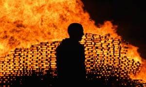 A man is silhouetted in front of the Sandy Row bonfire