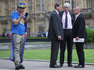 Andrew Mitchell, a former Conservative party chief whip, speaks to former attorney general Dominic Grieve, as an anti-Brexit protester stands near them opposite the Houses of Parliament in London on 10 May.