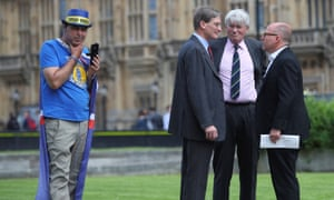 Andrew Mitchell, Dominic Grieve and another man in a suit speak as an anti-Brexit protester stands nearby