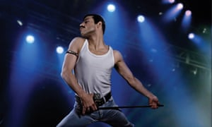 Rami Malek in a white vest and jeans, striking a classic Freddie Mercury pose