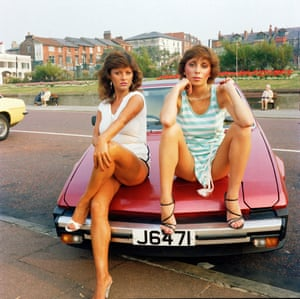 Two women pose on the bonnet of a sports car. Taken from Looking for Love 1978-2003
