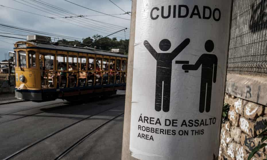 A tram passes by a sign warning of armed robberies.