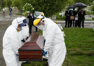Cemetery and funeral workers carry the coffin containing the remains of a man who died of Covid-19 at the Zipaquira's Park Cemetery in Zipaquira, Colombia, Friday, 18 June 2021.