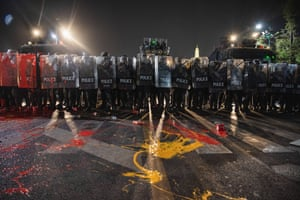"""Bangkok, ThailandRiot police with paint on their shields and on the ground stand in formation during the demonstration demanding monarchy reforms. Pro-democracy protesters gathered at the Democracy Monument before marching to the Bangkok City Pillar Shrine near the Royal Grand Palace to demand the reform of the monarchy and release 4 Activists (Somyot Pruksakasemsuk, Patiwat Saraiyam, Parit """"Penguin"""" Chivarak and Anon Nampa) who were arrested because of the lese majeste law (article 112)"""