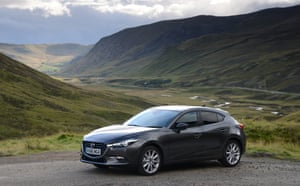 Mazda 3 2.0 parked in front of mountain scenery