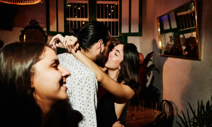 two people kissing at a party, posed by models