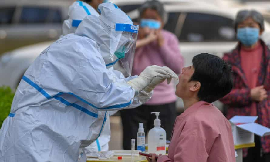 A medical worker collects a throat swab at a residential community in Shulan, north-east China's Jilin Province, where an outbreak has been reported.