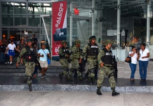 Mexican soldiers evacuate civilians from a shopping mall after reports of gunfire.