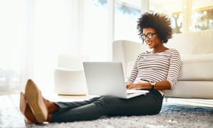 A woman on her laptop while being seated on the floor at home.