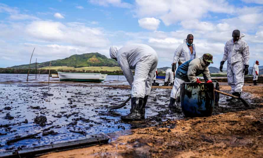 People in white protective overalls and rubber boots working with tools and containers on a heavily polluted beach