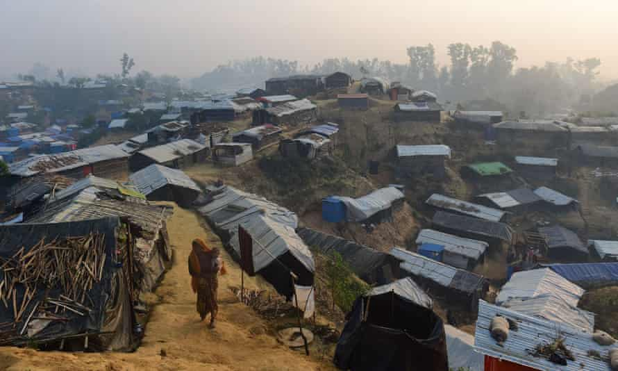 A Rohingya refugee woman walks with a child in the Balukhali refugee camp in the Bangladeshi district of Ukhia