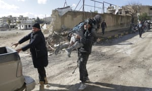 A man carries an injured woman in a site hit by what activists said were airstrikes carried out by the Russian air force in the rebel-controlled area of Maaret al-Numan town in Idlib province, Syria, on Saturday.