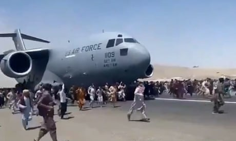 People run after and cling to a moving US military plane leaving Kabul airport.