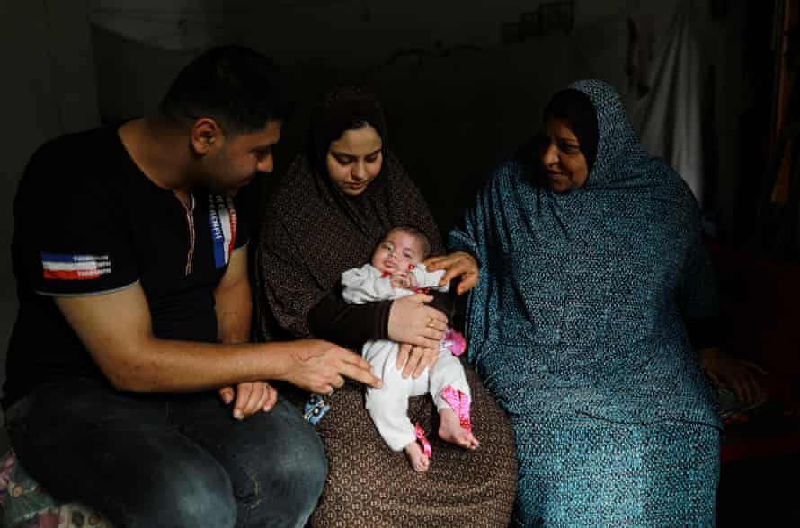 Hiba Swailam carrying her daughter Shahad, with husband Mohammad and her mother in law Khadra in Beit Lahia.