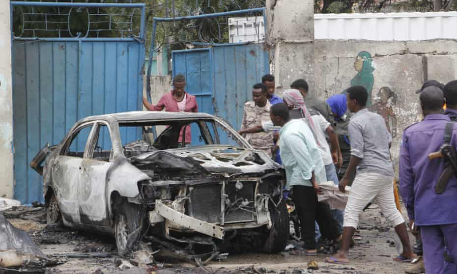 People gathered around burnt-out car.