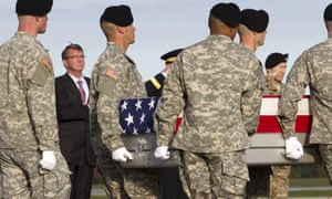 The US defense secretary, Ash Carter, watches as soldiers carry the remains of Sgt Joshua Wheeler, who was killed during the rescue.
