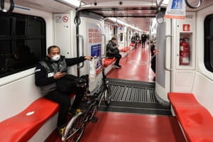 A man wearing a mask travels on the metro in Milan