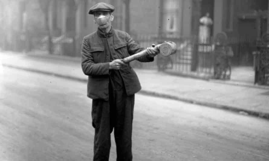 A man prepares to spray 'Anti-Flu' disinfectant on London buses in 1920.