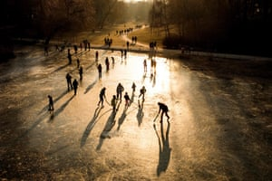 Berlin, Germany. The sun sets as people play on a frozen pond in a park next to Schöneberg town hall