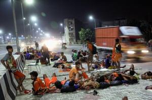 New Delhi, India: Hindu devotees of Lord Shiva rest under a flyover near the Akshardham temple